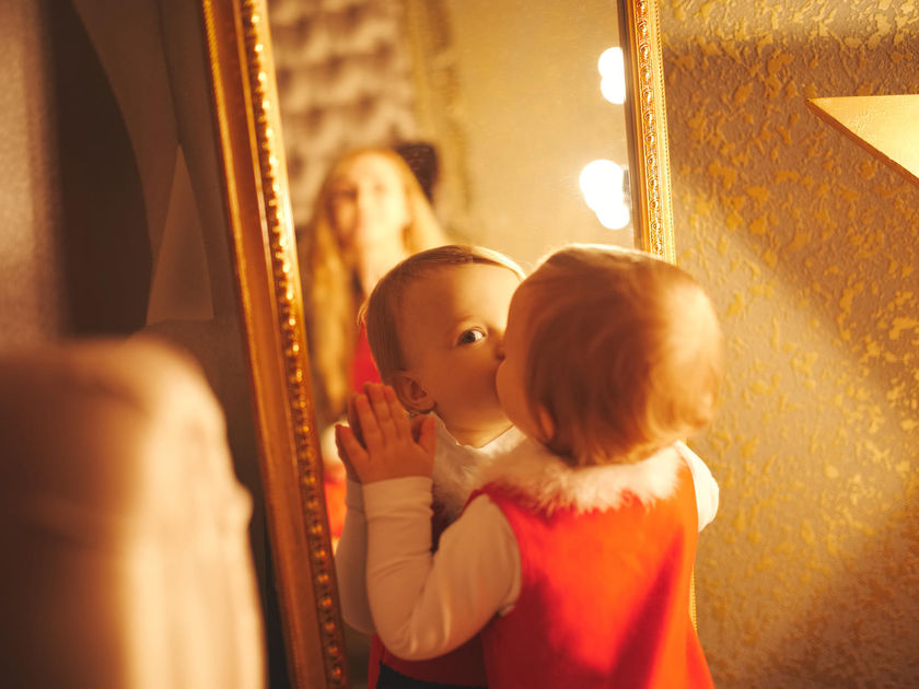 Little Girl Kisses Her Reflection in Mirror
