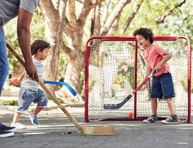 Father and Sons Playing Street Hockey