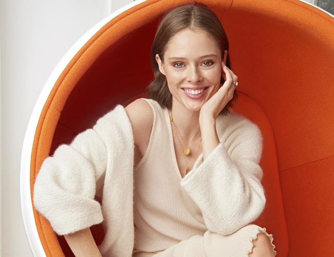 Coco Rocha sitting in orange chair