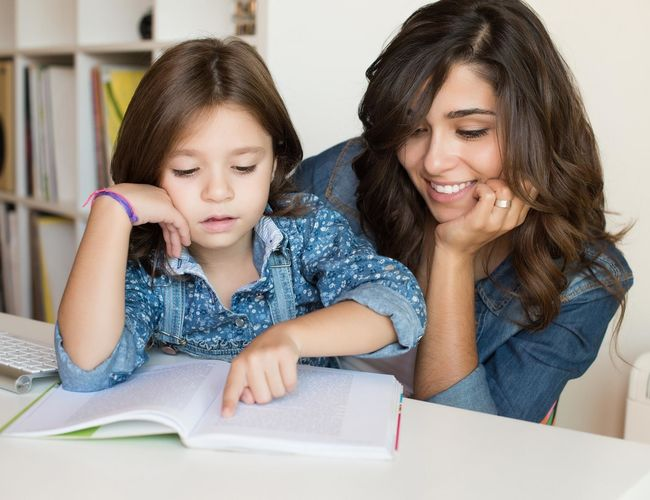 Latin Mom and Daughter Reading From Book