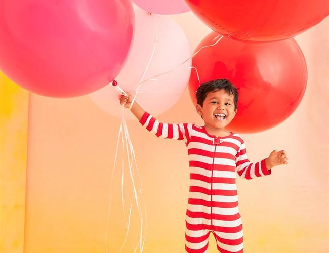 DIY Costume Boy in striped onsie holding balloons