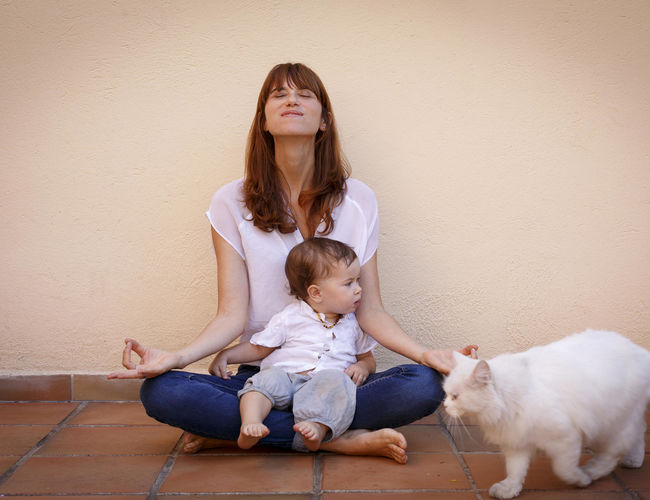 Self Care: Mom practicing yoga with baby daughter on floor