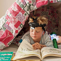 Kid reading under the covers