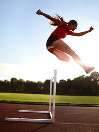 Woman jumping hurdle