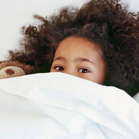 Girl snuggled in bed with teddy bear