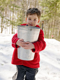 child carrying bucket of maple syrup