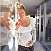 Cheerful pregnant woman leaning against glass wall