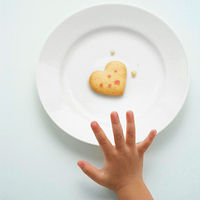 Child reaching for heart-shaped cookie
