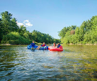 4 people in tubes on river