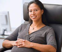 pregnant businesswoman sitting in office chair