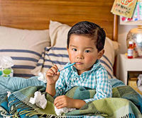 Boy in bed with thermometer