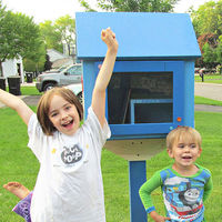 Two kids in front of a blue little library