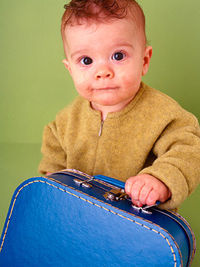 Toddler holding blue suitcase