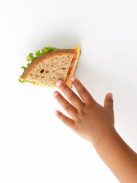 child reaching for a sandwich
