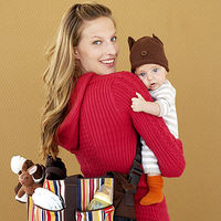mother holding baby and diaper bag