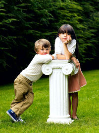 boy and girl leaning on a pedestal