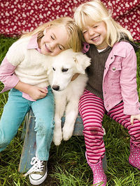 girls hugging dog