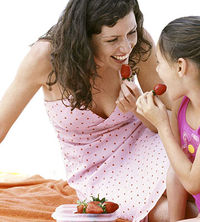 mother and daughter eating strawberries