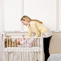 mother putting baby in crib