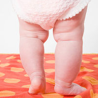 baby standing on red and orange fabric
