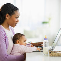 woman holding baby typing on computer