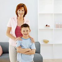 Red haired mom standing over freckled son, smiling