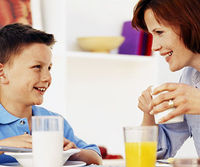 Red haired mom and freckled son smiling at breakfast table