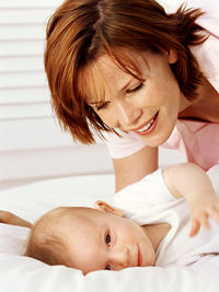 Red haired mom with baby lying down on side, smiling