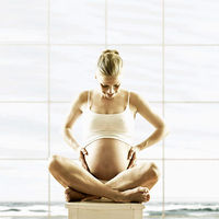 pregnant mom in tank top sitting cross legged with belly showing