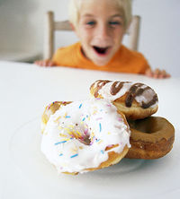 kid smiling at pile of donuts