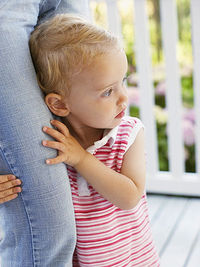 child clinging to mothers leg