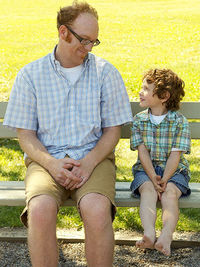 father and son talking on park bench
