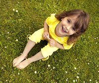 Little girl with gold earrings sitting on grass, holding white flower