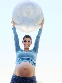 pregnant woman holding exercise ball