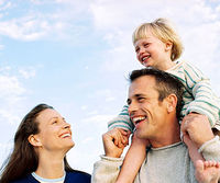 Mom smiling up at dad with daughter on his shoulders, outside