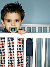 boy standing in crib sucking on pacifier