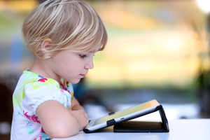 little girl playing with ipad