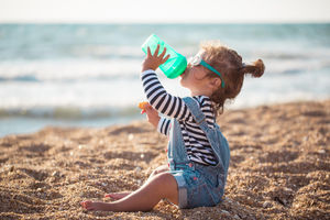 baby drinking from bottle at beach