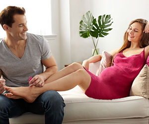 husband painting pregnant wife's toenails