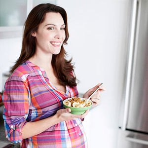 Pregnant woman eating breakfast