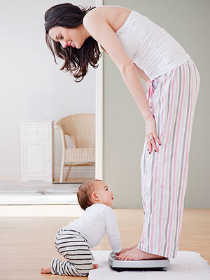 woman on scale with baby crawling up to her