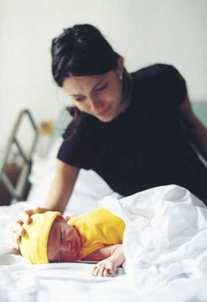 mother looking at baby in yellow hat and clothes