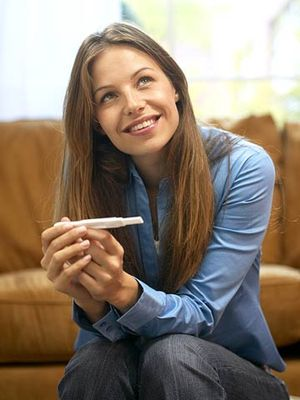 young woman holding pregnancy test looking away with smile