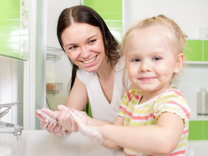 parent helping child wash hands