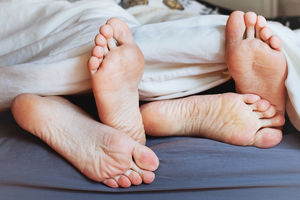 Couple's feet under covers in bed