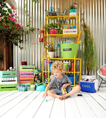 Kid sitting in front of yellow shelf full of bins and stuff