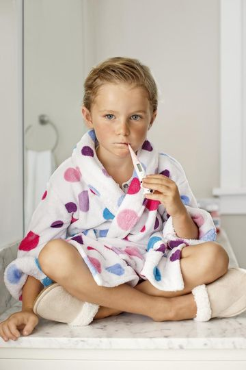 Child in Polka-Dot Robe with Thermometer in Mouth