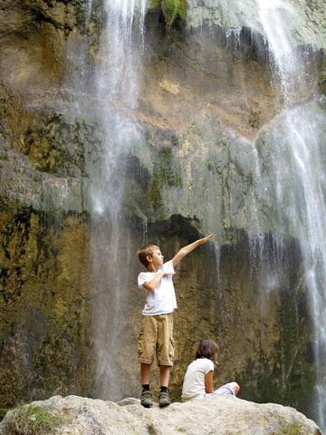 Boy in front of waterfall in Croatia