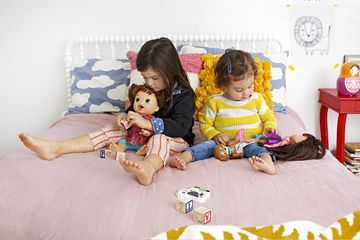 Brunette Toddler Playing with Dolls