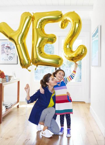 Mom and daughter holding balloon that says yes